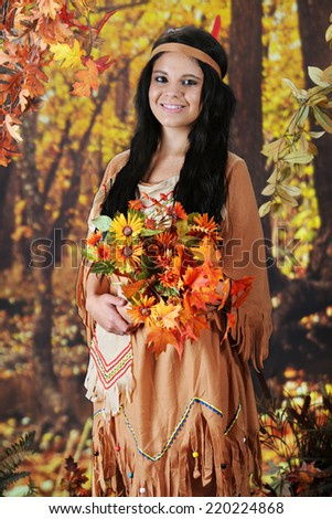 A beautiful teen Indian maiden holding a bouquet of flowers that she's found near a colorful autumn woods. - stock photo