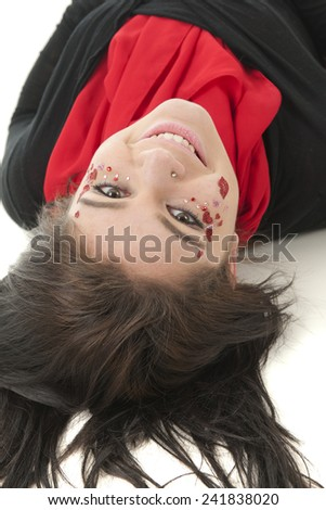 A beautiful teen looking back at the viewer as she lays on her back.  She's wearing red and black and her face is decorated in sparkly hearts, rhinestones and a pair of lips.  On a white background. - stock photo