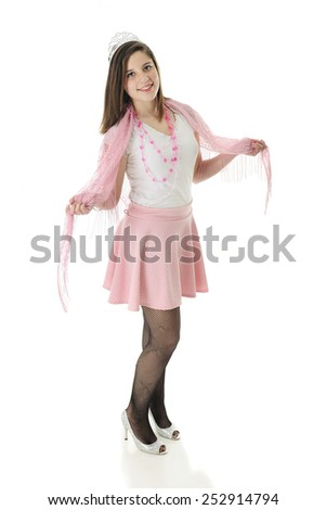 "A beautiful teen ""princess"" happily posing in the silver crown and shoes, and pink skirt, lacey shawl and necklace of hearts.  On a white background."