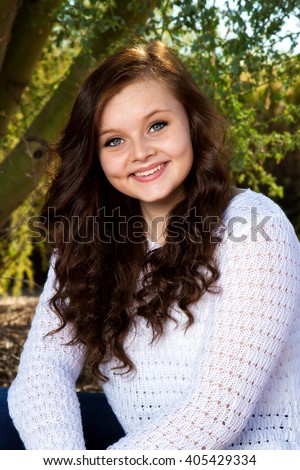 A beautiful teenage girl with big, blue eyes, dimples, and brown hair poses for a portrait. - stock photo