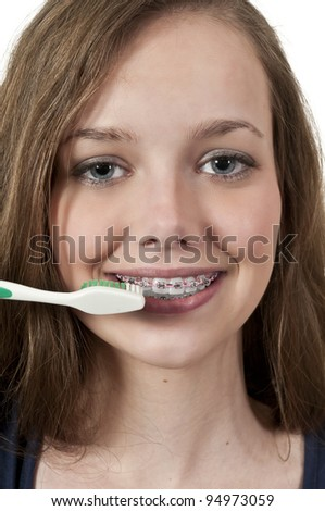 A beautiful teenage woman practicing good oral dental care by brushing her teeth - stock photo