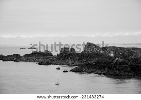 A beautiful view from Pointe du Grouin with sailboat and lighthouse. Brittany, France. Aged photo. Black and white. - stock photo