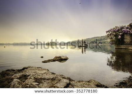 A beautiful view of lake of Pusiano, Italy at sunset during a cloudy spring day