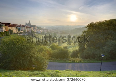 A beautiful view of Prague at sunrise on a misty morning ~ A panorama of Prague Old Town with majestic Prague Castle and St. Vitus Cathedral on the left and a golden rising sun in the background - stock photo