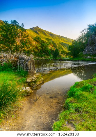 A beautiful view of the river Dove and stepping stones in the distance at Dovedale in the English Peak District