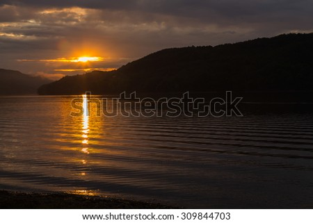 A beautiful view of the river. Great river under the sun. Grass and bushes on the banks of the river. Beautiful evening landscape.