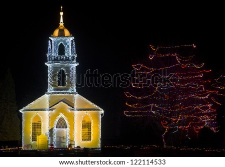 A beautiful village church with bell tower, decorated for Christmas.