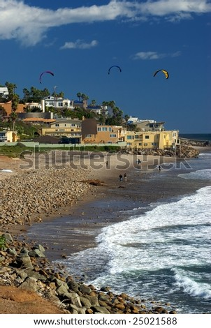 A beautiful vista of County Line Beach in Malibu, with surfers, waves and beautiful houses in the background