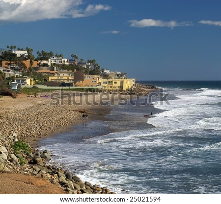 A beautiful vista of County Line Beach in Malibu, with surfers, waves and beautiful houses in the background - stock photo