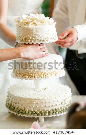 A beautiful wedding cake decorated with green and white pearls - stock photo