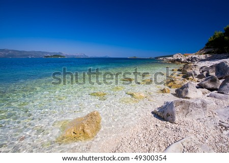 A beautiful white stone beach with clear blue water off the coast of Korcula.