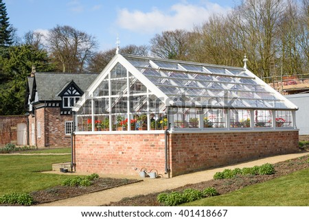 A beautiful white wooden greenhouse with an array of flowers and plants