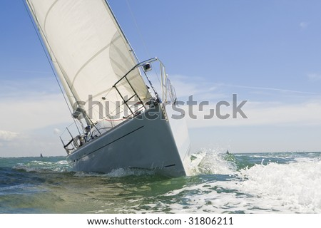 A beautiful white yachts racing close to the camera on a bright sunny day - stock photo