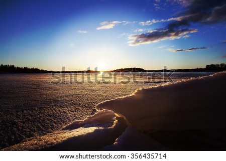 A beautiful winter day by the lake. Some snow is piled up in the front and a beautiful sunset is on the background. Some clouds are in the sky. Image has a vintage and light flare effect applied. - stock photo