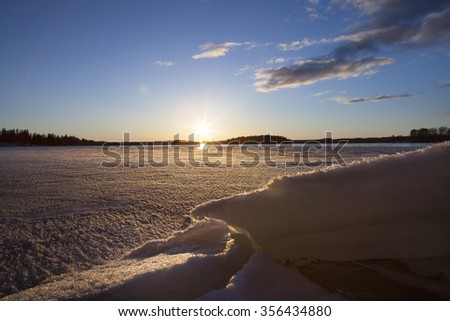 A beautiful winter day on the lake. Some snow is piled up in the front and a sun is about to go down in the background. Some clouds are in the sky. Image has a light flare added. - stock photo