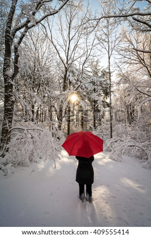 A beautiful winter sunrise snow scene with a woman walking with a red umbrella casting a long shadow from the sun. - stock photo