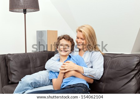 A beautiful woman and her teenage son at home, sitting on a couch cuddling. - stock photo