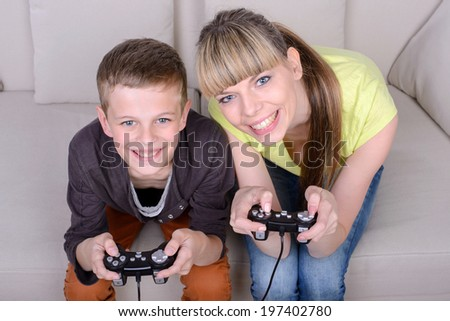A beautiful woman and her teenage son at home, sitting on a couch playing a video game.