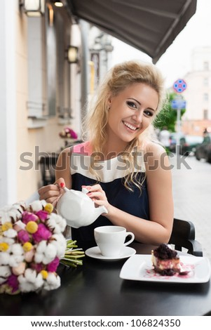 A beautiful woman are pouring tea. Holding a cup of tea. Outdoors - stock photo