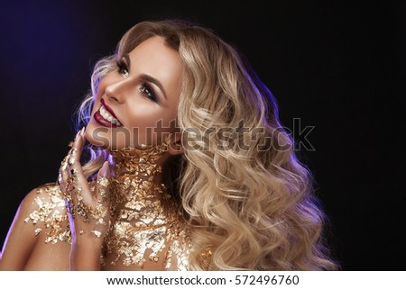 A beautiful woman , blond wavy hair , professional make-up , the color of gold , beauty fashion model clean skin close-up portrait . Body gold pattern.