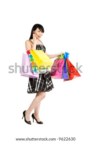 A beautiful woman carrying shopping bags while talking on the phone - stock photo