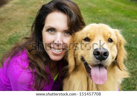A beautiful woman close to her handsome golden retriever dog - stock photo