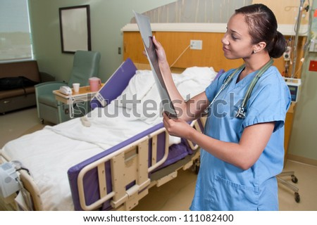 A beautiful woman doctor radiologist in scrubs holding an x-ray - stock photo