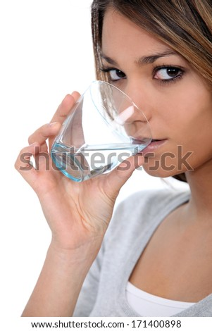A beautiful woman drinking a glass of water.