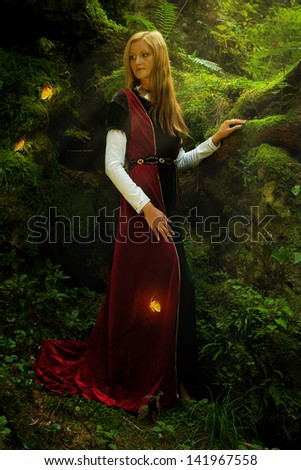 A beautiful woman fairy with long blonde hair in a historical gown is turning her head just to have a glimpse of shining golden butterflies flying around her in the deep woods  - stock photo