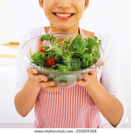 A beautiful woman holds a salad