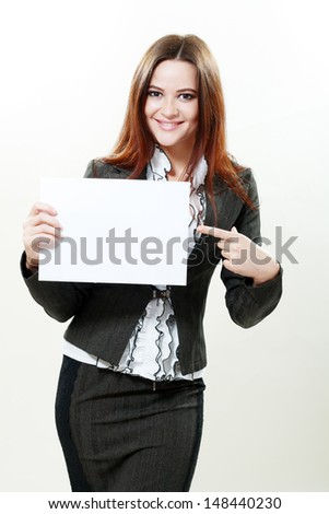A beautiful woman holds out an empty card studio shot