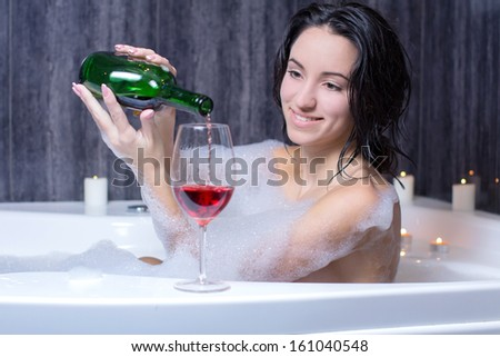 A beautiful woman in a bath with foam drinking wine