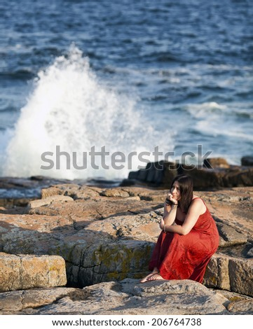 A beautiful woman in a red dress sits thinking on a rocky beach at sunset, while large waves crash against the rocks in the background. - stock photo