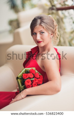 A beautiful woman in a red dress with a bouquet of red roses.