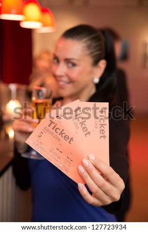 A beautiful woman in a theater, concert or cinema presenting tickets - stock photo