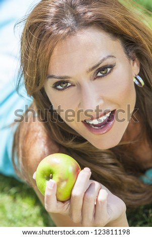 A beautiful woman in her thirties laying down outside on grass holding or eating an apple smiling with perfect teeth - stock photo