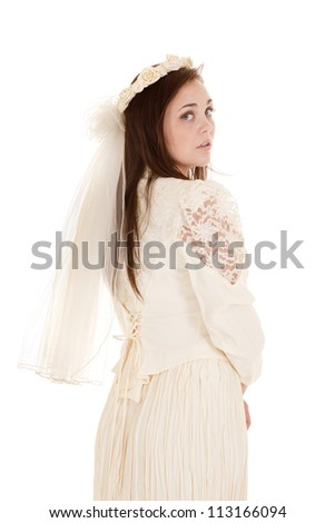 A beautiful woman in her vintage wedding dress looking over her shoulder - stock photo