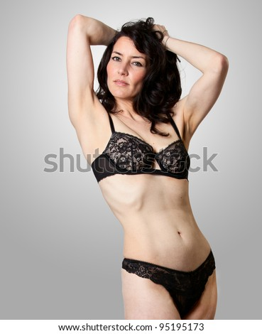 A beautiful woman in lingerie posing in studio - stock photo