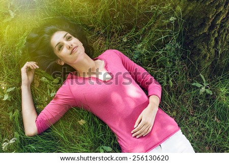 A beautiful woman is laying on her back in the grass, looking at the sky. She is relaxing, enjoying the shadow of the tree in a sunny day. - stock photo