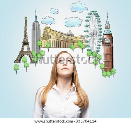 A beautiful woman is looking up by dreaming about the visiting of the most famous places in the world. The concept of tourism and sightseeing. Light blue background. - stock photo