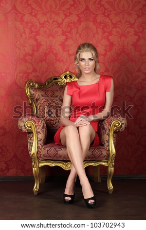 A beautiful woman is sitting in a antique chair against the red wall