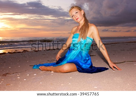 A beautiful woman is sitting on the beach infront of a beautiful intensely colorful sunset looking towards the viewer in this tropical feeling scene. - stock photo