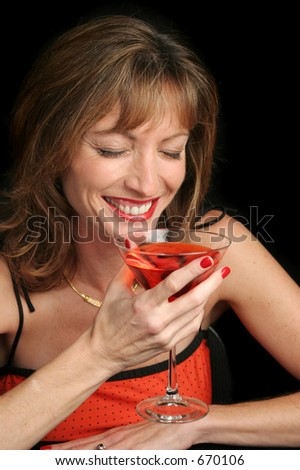 A beautiful woman laughing over a cocktail.
