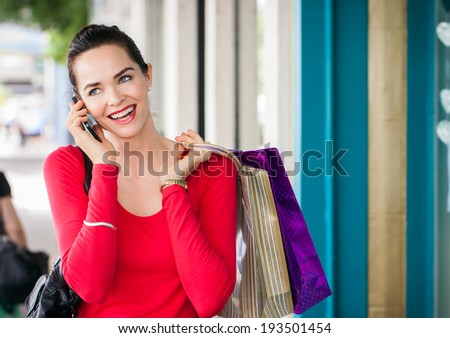 A beautiful woman out shopping is talking on her mobile phone. - stock photo