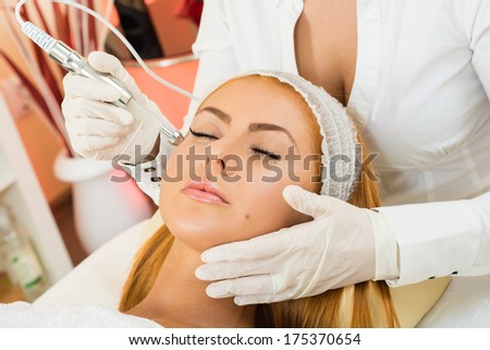 a beautiful woman receiving a facial treatment - stock photo