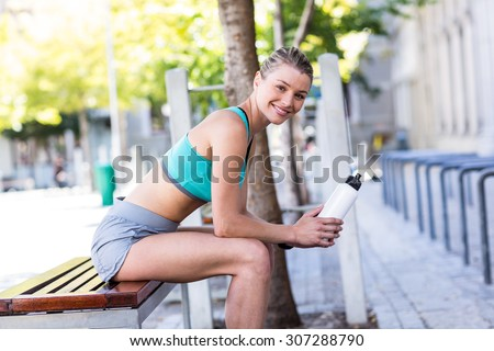 A beautiful woman sitting and holding a bottle on a sunny day - stock photo
