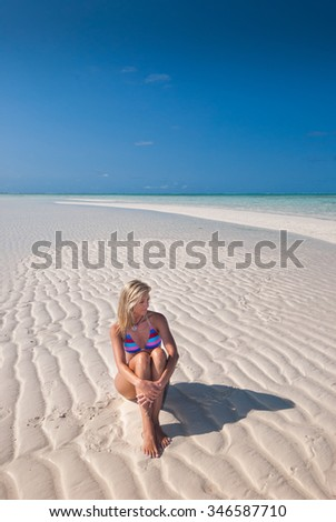 A beautiful woman sitting on a rippled empty beach with white sand, clear water and a blue sky