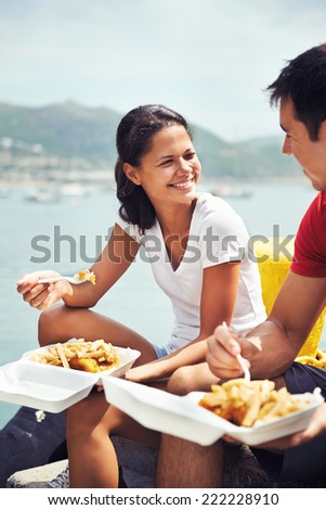 A beautiful woman smiling at her partner as they eat fish and chips by the harbour - stock photo