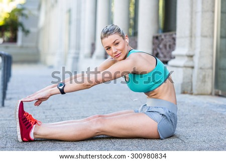 A beautiful woman stretching her leg on a sunny day - stock photo