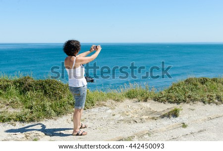 a beautiful woman takes a picture of the ocean
